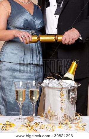 A couple in evening dress pulling a gold Christmas cracker at a Champagne party.