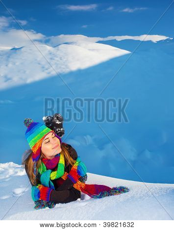 Picture of pretty woman laying down on snowy mountains, young lady wearing colorful hat with scarf, winter resort, mountain covered with snow in wintertime, Christmas holidays