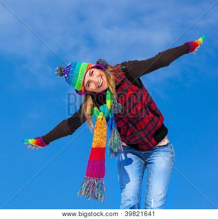 Picture of cute cheerful girl enjoying winter holidays, pretty young lady playing outdoors in winter cold weather, smiling woman with raised up hands isolated on blue sky background, Christmas holiday