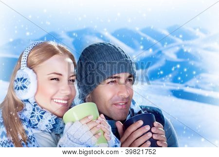 Picture of happy couple drink hot chocolate outdoors, beautiful woman with handsome man enjoying view of mountains covered white snow and holding cups of tea in hands, loving family, Christmas time