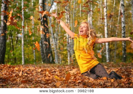 beautiful blonde Scatters Blätter in Holz im Herbst