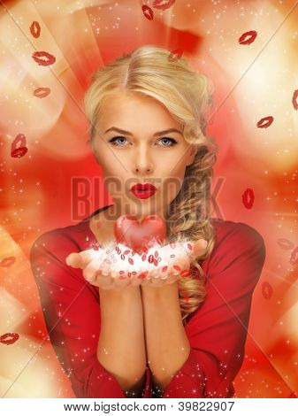 lovely woman in red dress blowing kisses on the palms of her hands