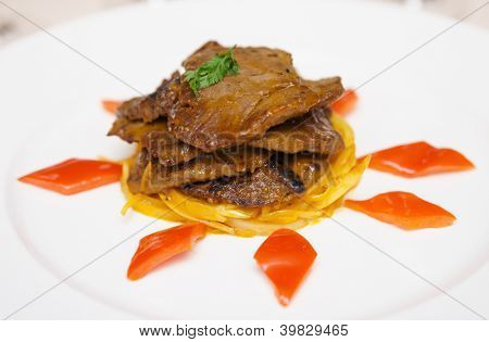 Fried venison with onion in porcelain plate close-up