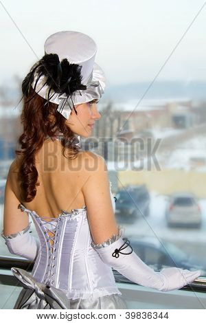 Young beautiful girl in costume Tamer looks out the window