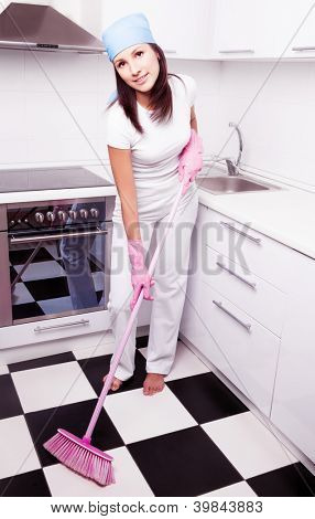 beautiful happy young housewife with a broom in the kitchen at home