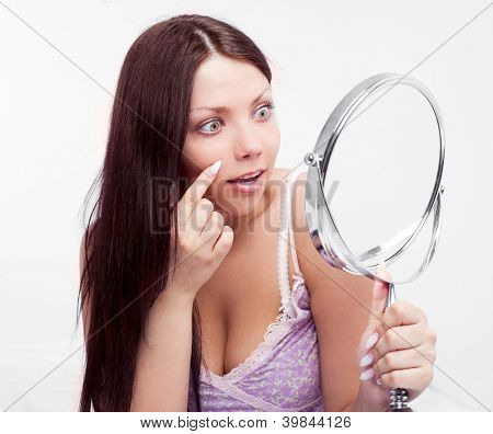 beautiful worried brunette woman having skin problems, with a mirror in bed at home