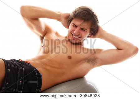 Handsome and sporty guy doing exercise for abs over a white background