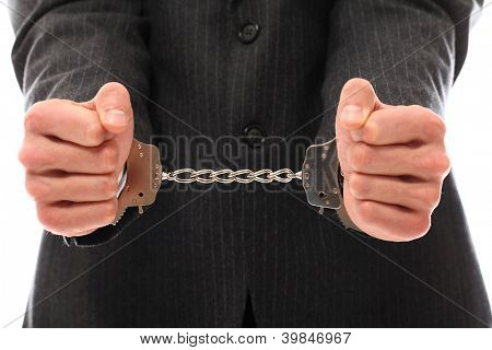 Close up of businessman hands in handcuffs over a white background