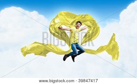 Young man dancing with yellow fabric over sky blue background