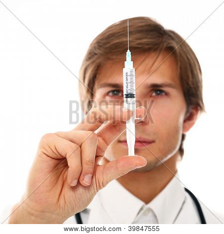 Young and handsome doctor holding syringe over a white background