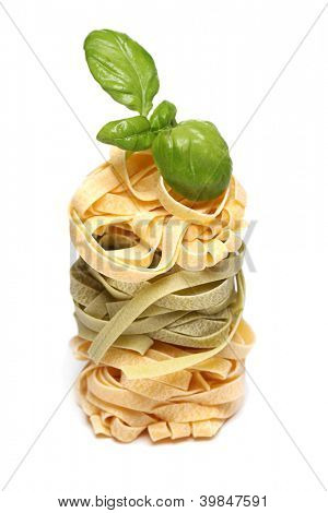 Dry pasta with fresh green basil over a white background