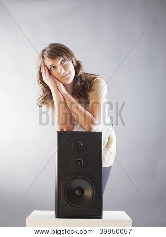 Young beautiful cheerful woman with hand on the big wooden speaker and listening music