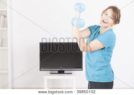 Woman doing fitness with dumb-bells at home using on screen TV instructions