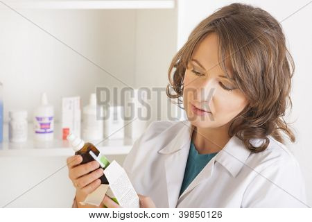 A cheerful young woman pharmacist with a bottle of medicine standing in pharmacy drugstore