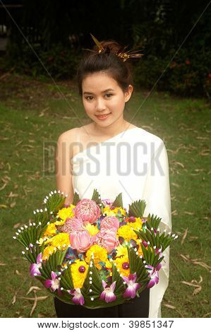 Pretty Woman In Thai Style Clothes In Posing Hold Flower Joist.