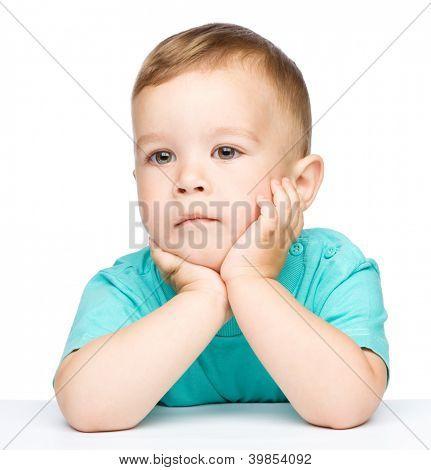 Porträt von ein netter kleiner Junge sitzend am Tisch unterstützen den Kopf mit den Händen, isolated over white