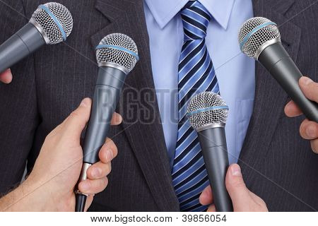Press conference with media microphones held in front of business man, spokesman or politician