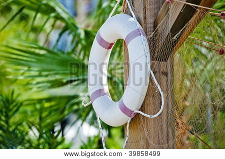White life preserver hanging on a wooden post