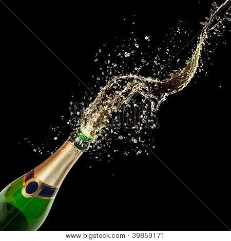 Celebration theme with splashing champagne, isolated on black background