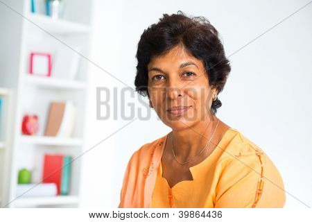 Portrait of a 50s Indian mature woman smiling, isolated on white background