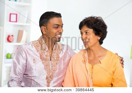 Indian mature mother talking with her adult son at home