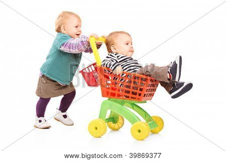 Toddler girl pushing her twin brother in a toy cart isolated on white background