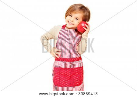 A smiling girl with apron holding a red apple isolated against white background