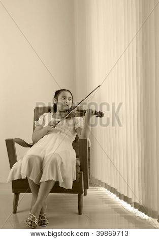girl playing violin at home studio sepia color tone
