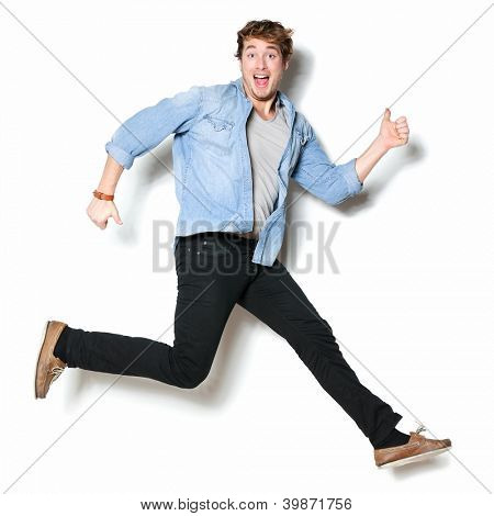 Jumping man happy excited. Funny portrait on young casual male male model in humorous jump on white background.