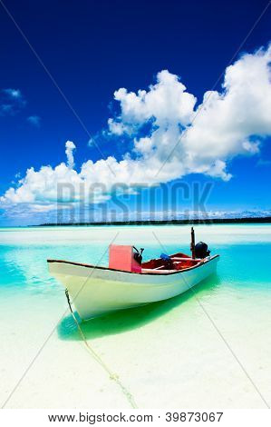 A beautiful tropical island beach with colourful boat in the foreground