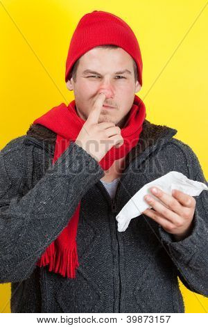 Ill young man with red nose, scarf and cap picking nose with hanky