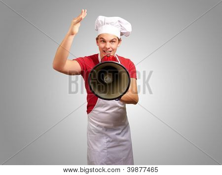 portrait of happy cook man shouting using megaphone over grey background