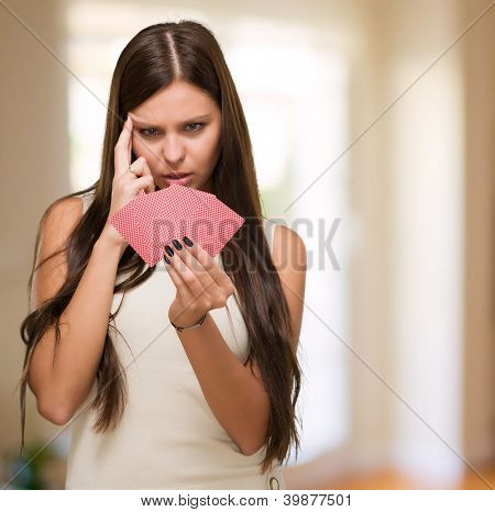 Confused Young Woman Holding Playing Cards at her home