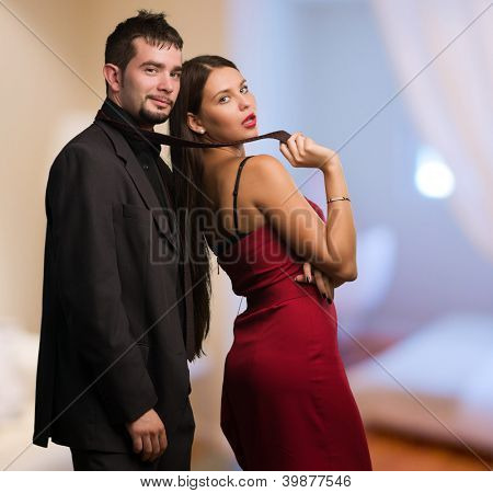 Beautiful Woman Holding Businessman Tie at a bedroom