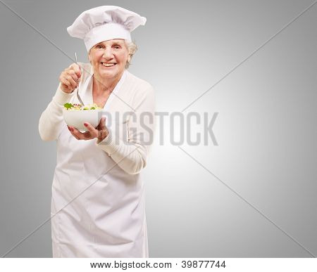 portrait of adorable senior cook woman eating salad against a grey background