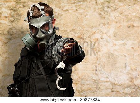 Soldat mit A Gasmaske Holding Handschellen gegen eine Steinmauer