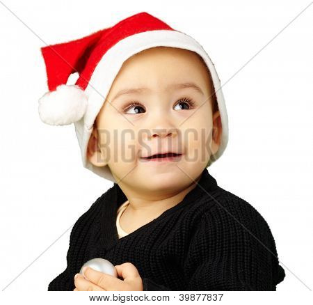 Baby boy wearing a christmas hat and looking up against a white background