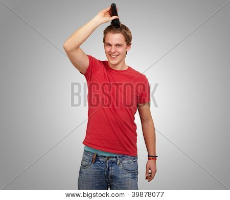 portrait of young man cutting his hair over grey background