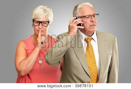 Man Taking On Cellphone In Front Of Woman Gesturing On Gray Background
