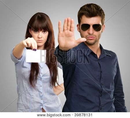 Man Showing Stop Sign In Front Of Woman Holding Placard On Gray Background