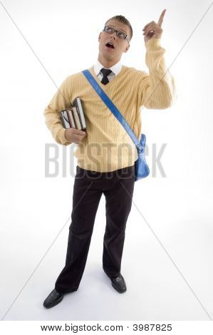 Young Student Carrying Bag And Books Pointing Upwards