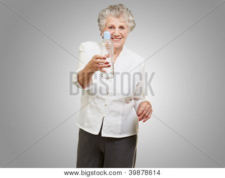 portrait of healthy senior woman holding a water bottle over grey background