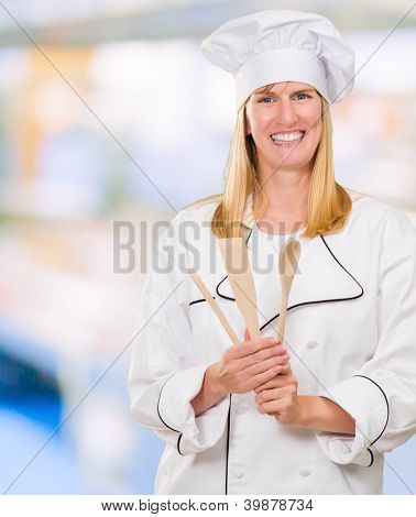 Female Chef Holding Wooden Spoon against an abstract background