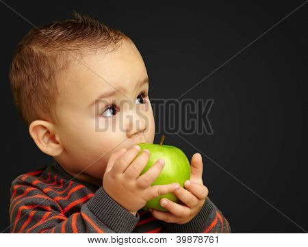 Portrait Of Baby Boy Eating Green Apple against a black background