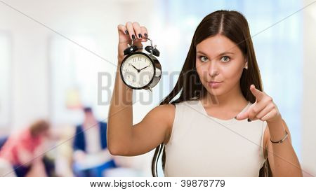Woman Holding Alarm Clock and pointing, indoor