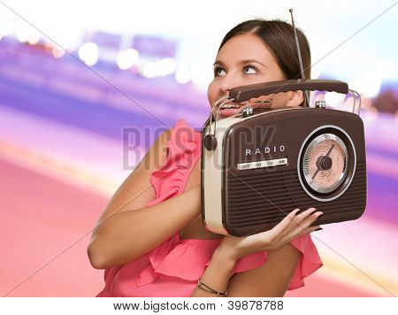 Portrait Of Happy Woman Holding Radio against a city by night