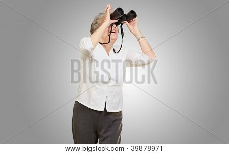 portrait of senior woman looking through a binoculars over grey background