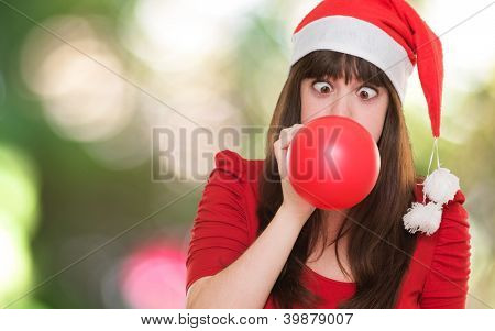 christmas woman blowing a balloon with her eyes crossed against a nature background