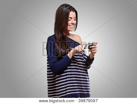 portrait of young woman touching a modern mobile over grey