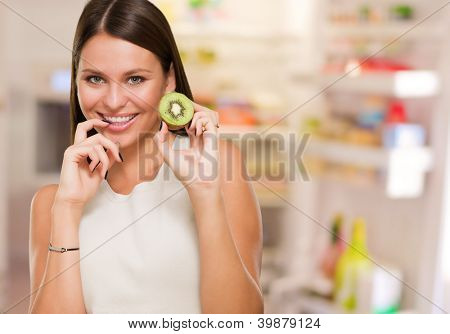 Portrait Of A Young Woman Holding Kiwi in front of a fridge